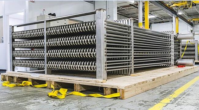 large bare-tube industrial heat exchanger in a factory setting