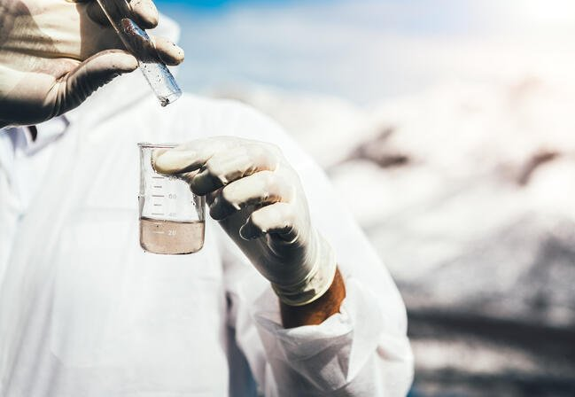 scientist in PPE testing water quality