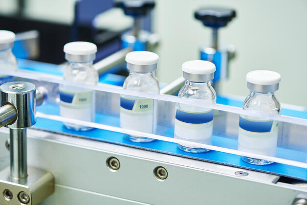 vials of vaccine on a conveyor belt at a pharmaceutical plant