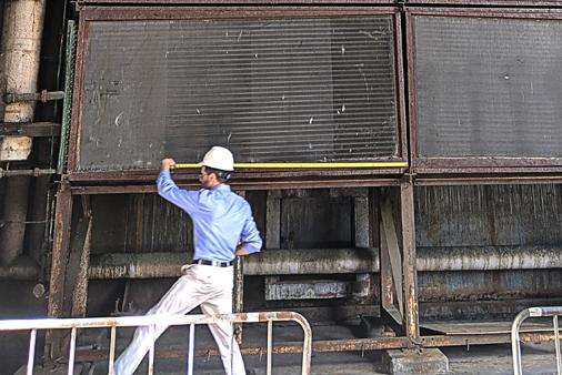 Engineer measuring industrial heat exchanger on-site