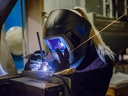 woman TIG welding an object