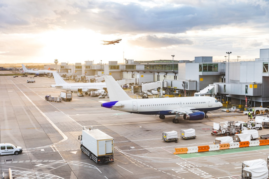 busy-airport-view-with-airplanes-and-service-vehicles-at-sunset-picture-id