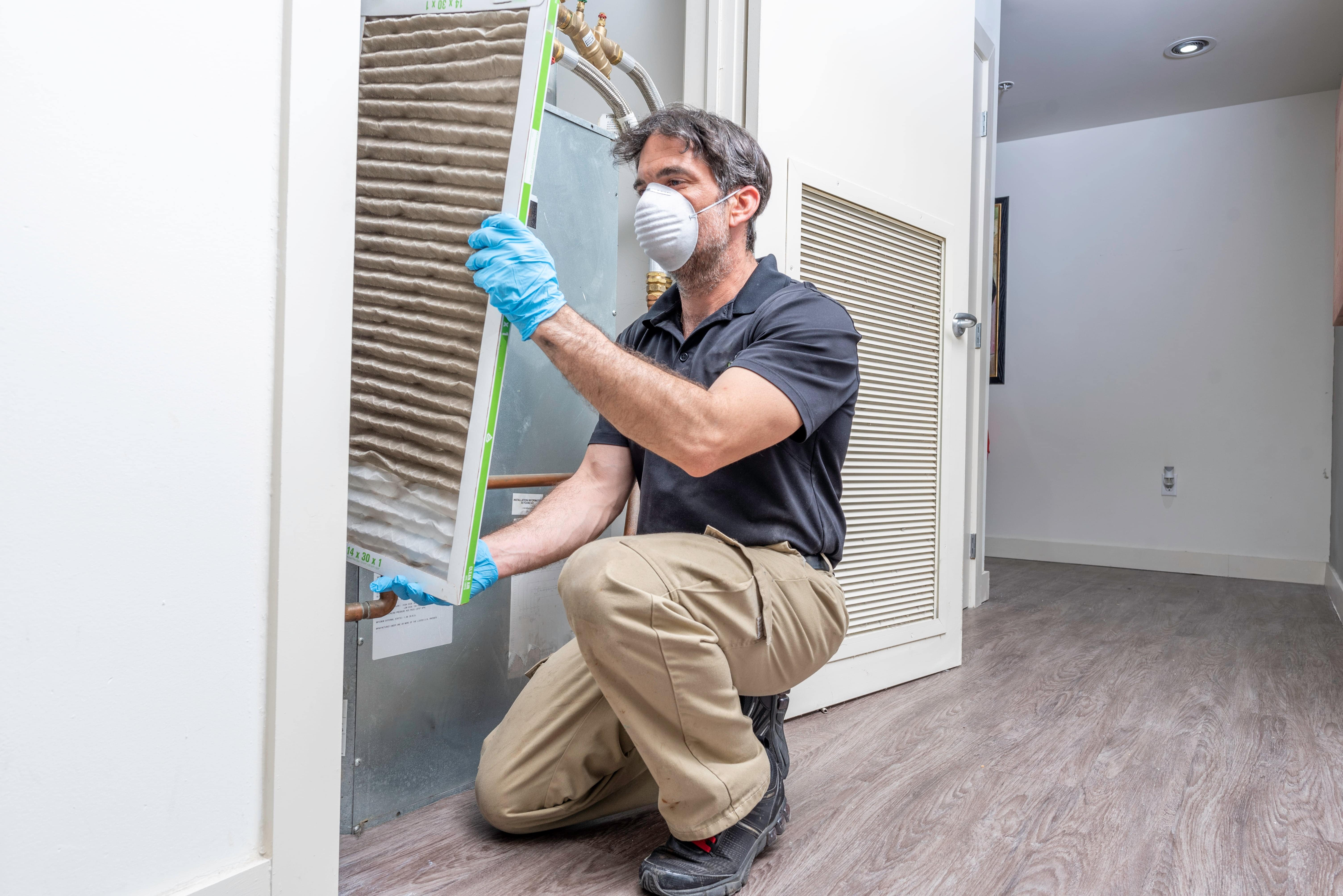 technician in a dust mask examines dirty heat pump air filter